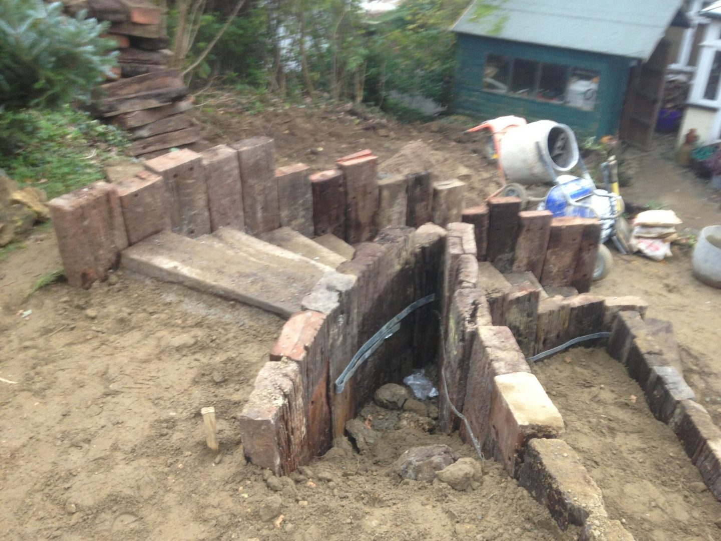 The beginnings of a sweeping garden staircase made from railway sleepers
