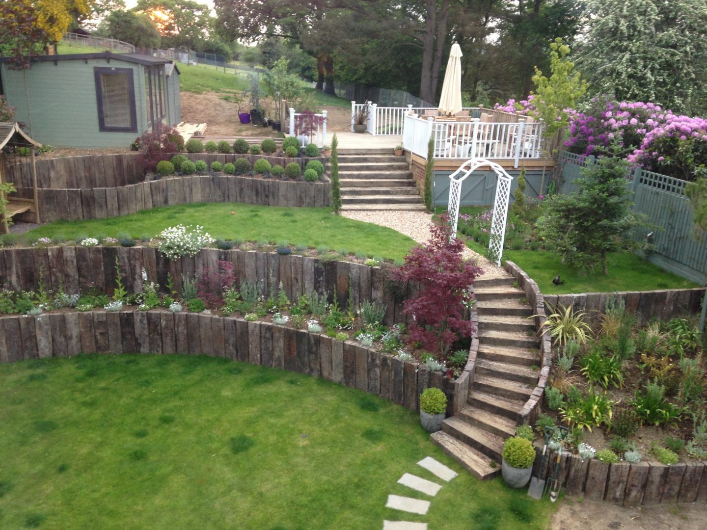 The sweeping garden staircase made of sleepers and with the initial planting either side.