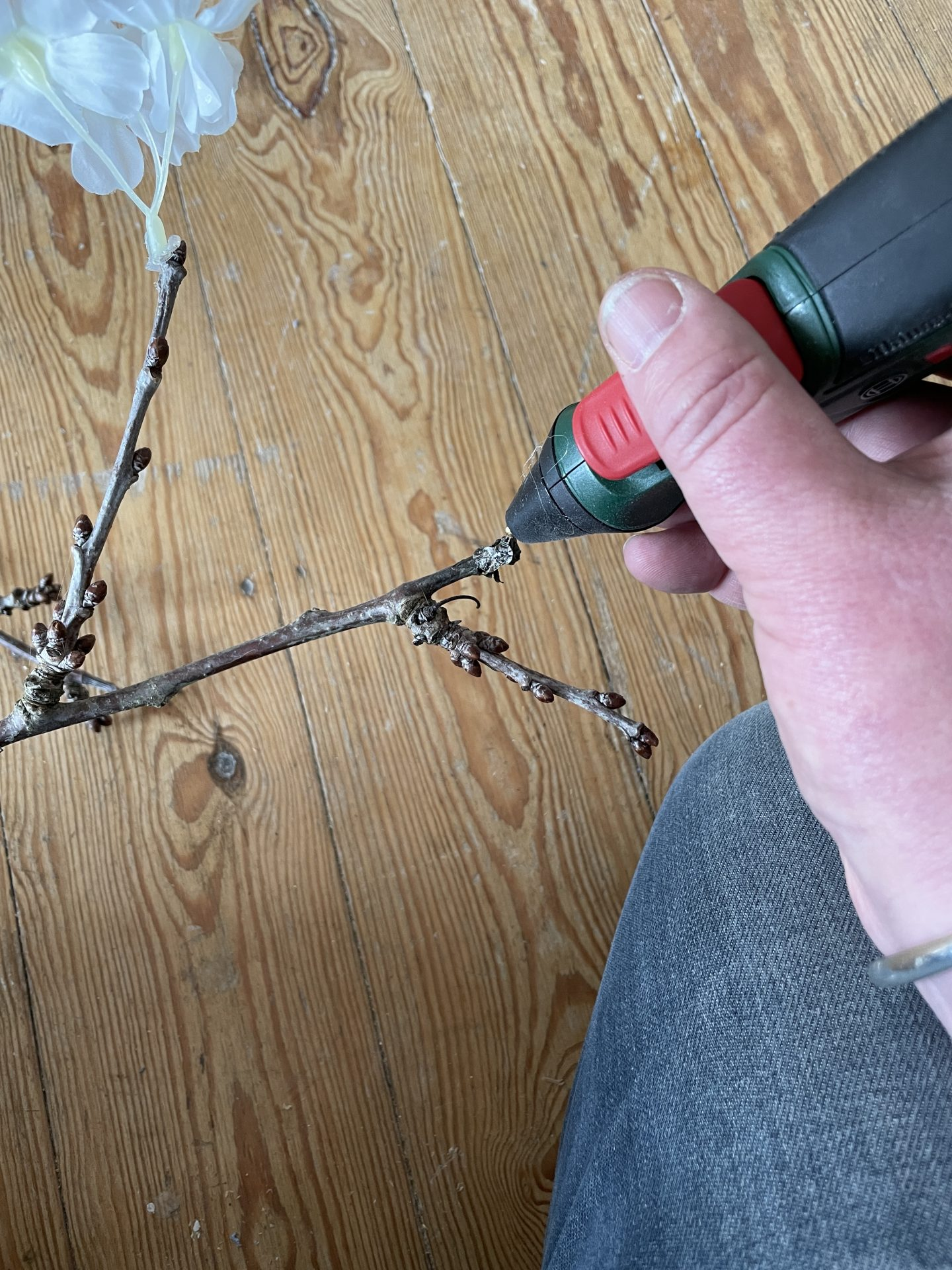 Glue gun - gluing faux cherry blossom onto a dead branch.