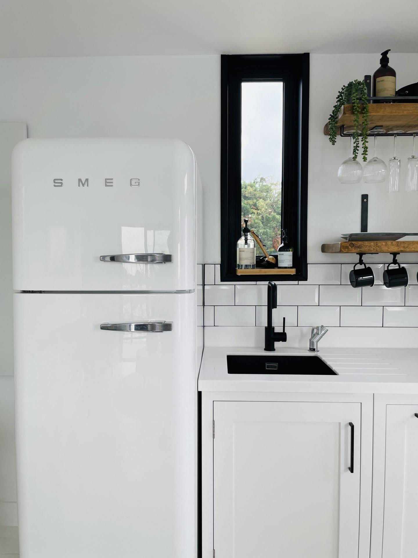White kitchen with white Smeg fridge.