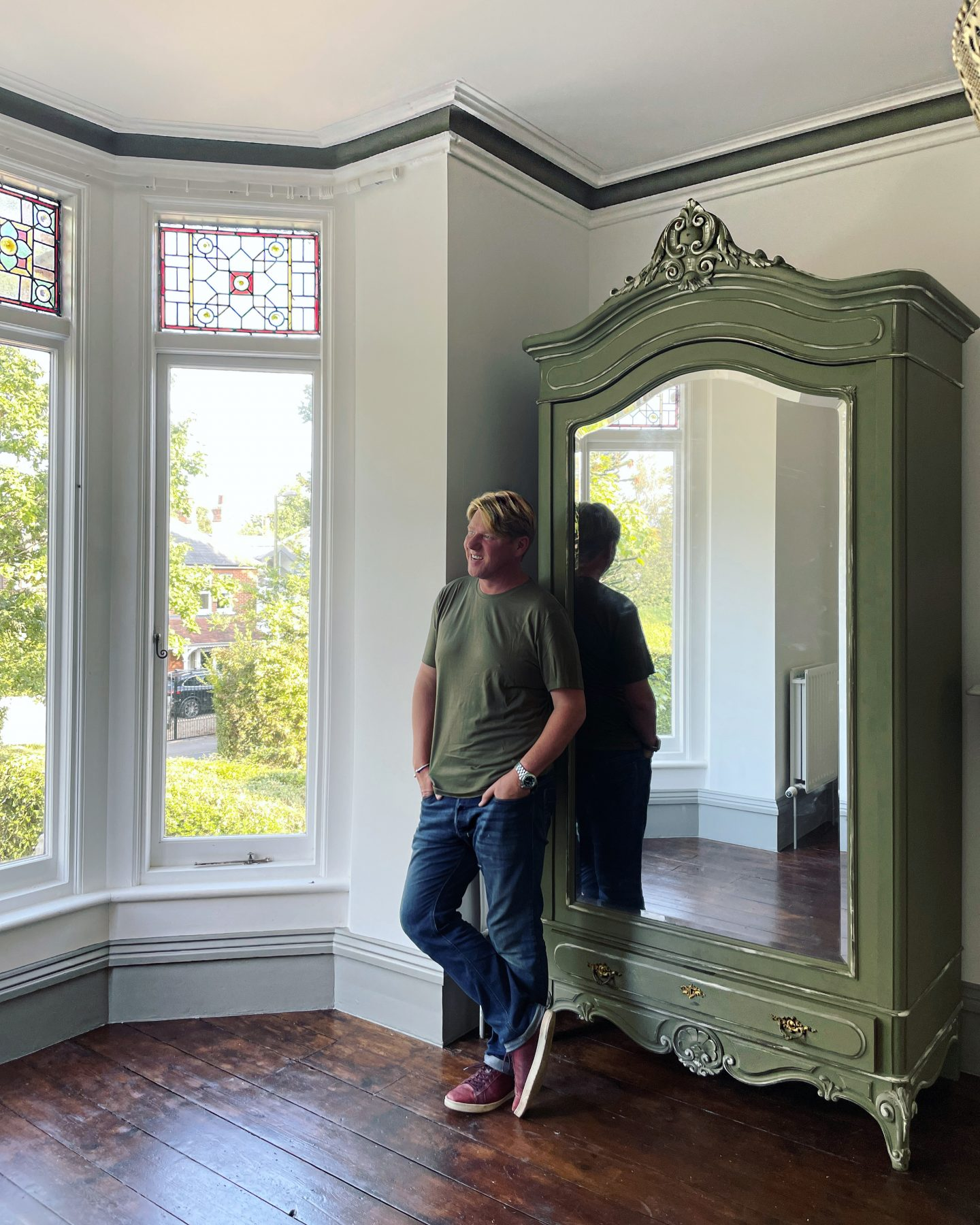 Large green armoire with Jp Clark standing next to it.