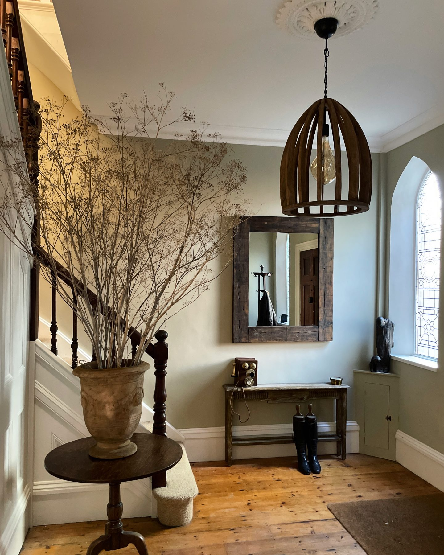 Hallway with arched windows and a large urn with cow parsnip in it.