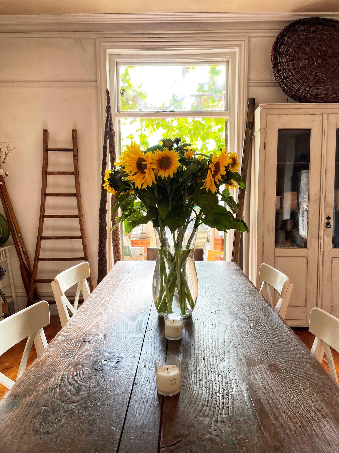 Sunflowers on a dark wood rustic table by Jp Clark jpslifeandloves